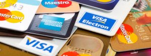 Close-up view of several VISA, MasterCard, and Amex credit cards strewn across a table