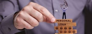 Close-up of man placing a 'Jenga' block with the blocks reading 'Personal Loan'