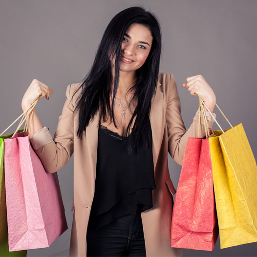 Young woman holding up several colourful shopping bags in both hands