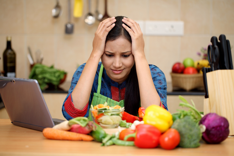Stressed homemaker holding her head at kitchen counter worrying about how to get the best loan in Singapore