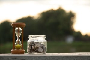 Hourglass and jar of coins representing an urgent cash loan Singapore