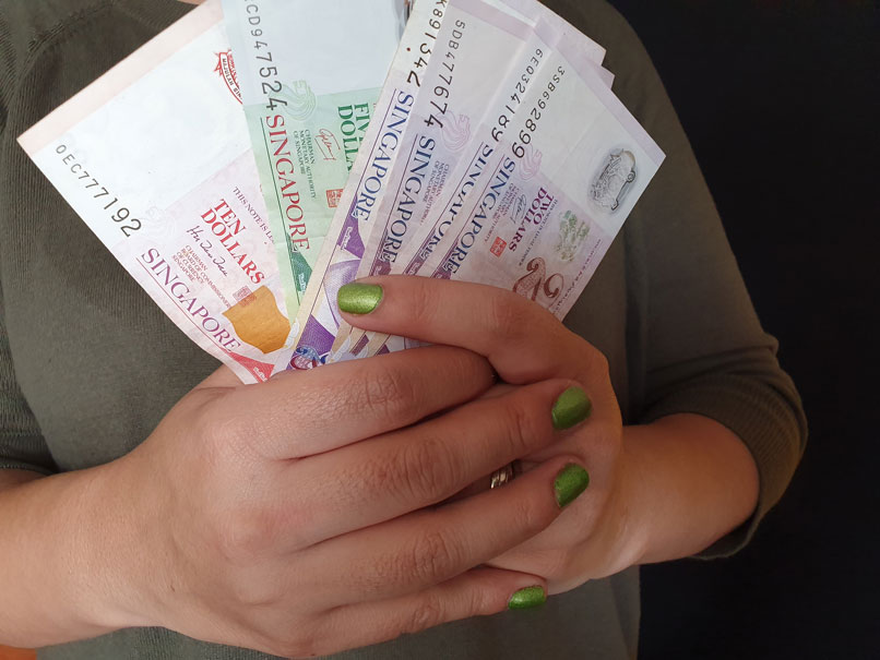 A woman holding Singapore dollar notes as she obtains urgent cash loan in Singapore